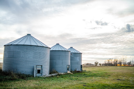 3 Grain bins in a grass filled field