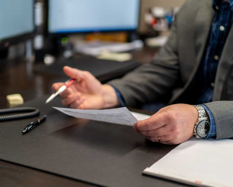 man in suit with a red pen holding a document at his desk