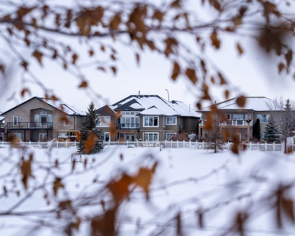 homes bordering a field in winter. Snow melt is one of the leading causes of spring flooding.