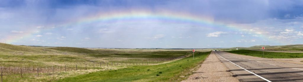 Rainbow over an open prairie road