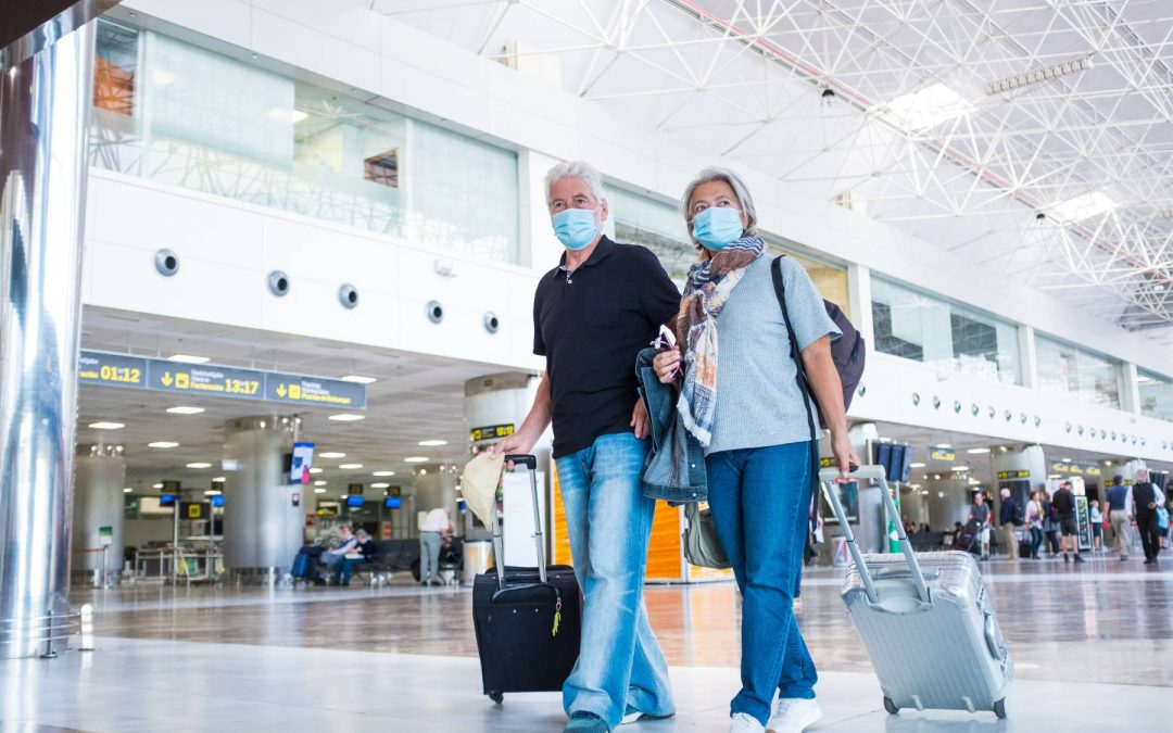 couple with covid masks on walking through airport